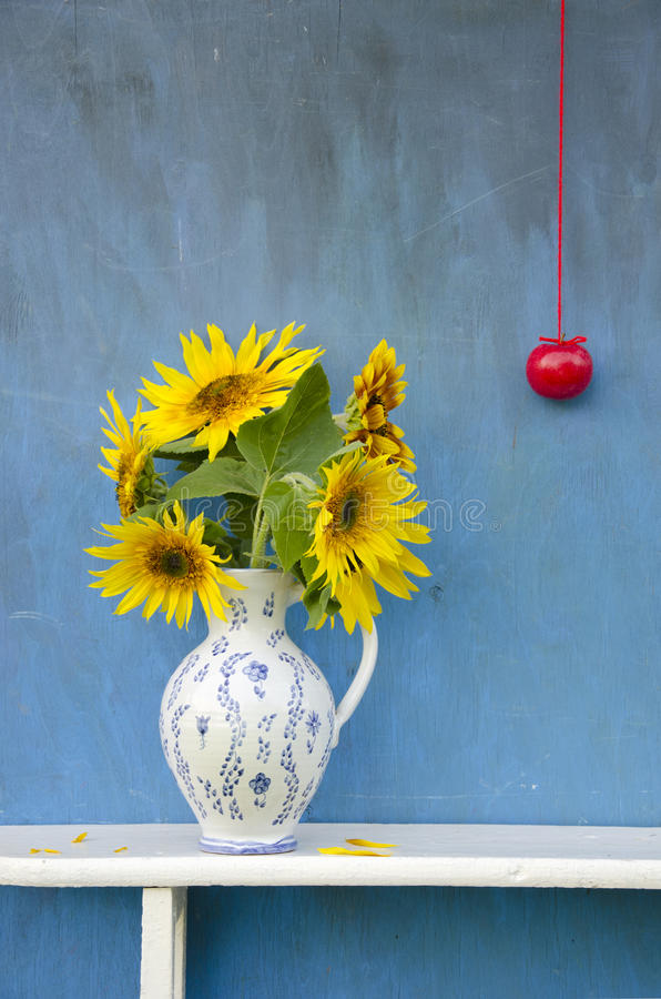 Ramalhete bonito dos girassóis do verão no jarro elegante com maçã vermelha fotografia de stock royalty free