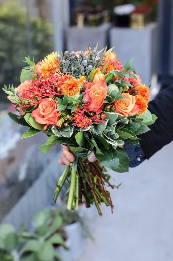 Ramalhete bonito nas cores alaranjadas corais das rosas, das tulipas, do multifida do Jatropha, do tinctorius do Carthamus e das  fotos de stock