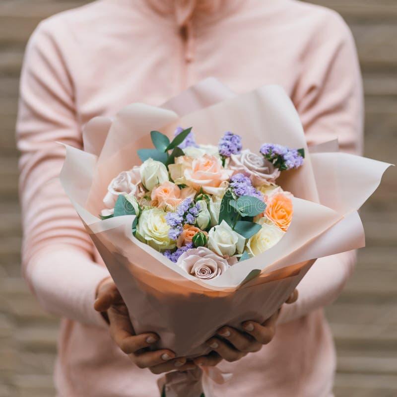 Ramalhete colorido de flores frescas diferentes nas mãos da mulher do florista Fundo rústico da flor Ramalhete do ofício de imagens de stock