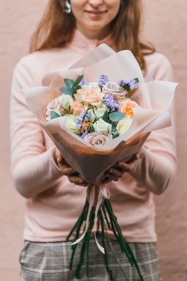Ramalhete colorido de flores frescas diferentes nas mãos da mulher do florista Fundo rústico da flor Ramalhete do ofício de imagem de stock