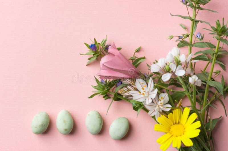 Ramalhete colorido pastel dos ovos de chocolate de flores do campo da mola em claro - fundo cor-de-rosa com textura de papel de l fotografia de stock