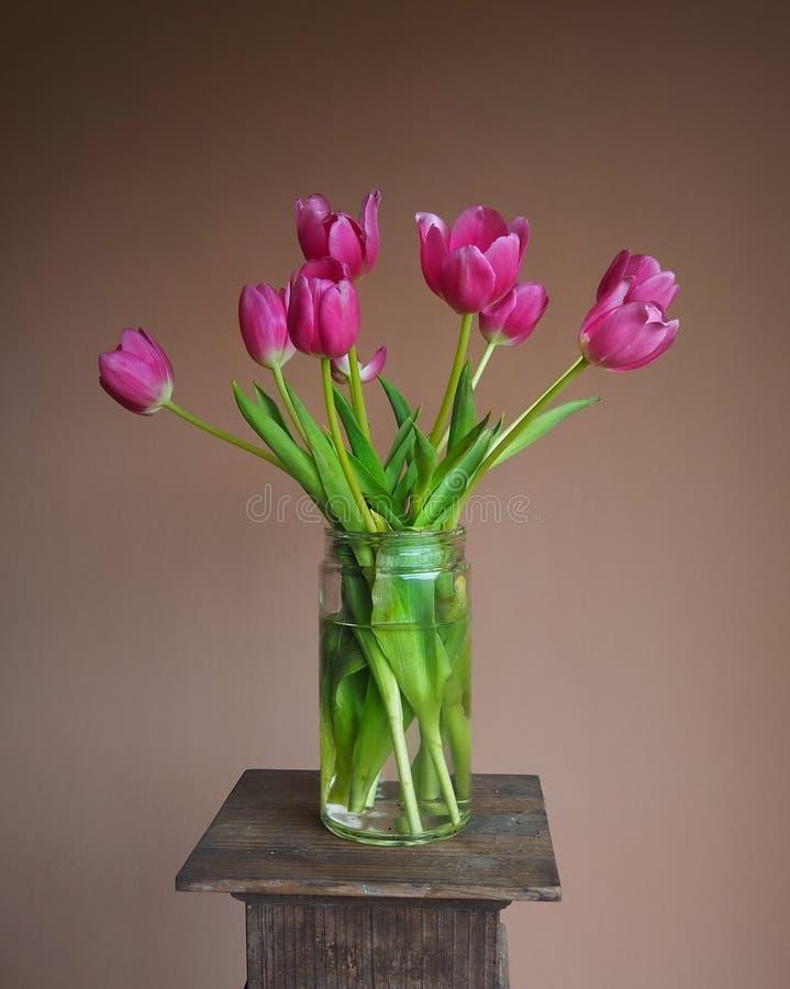Ramalhete cor-de-rosa brilhante da tulipa em um frasco de pedreiro em um suporte com fundo da terracota foto de stock royalty free