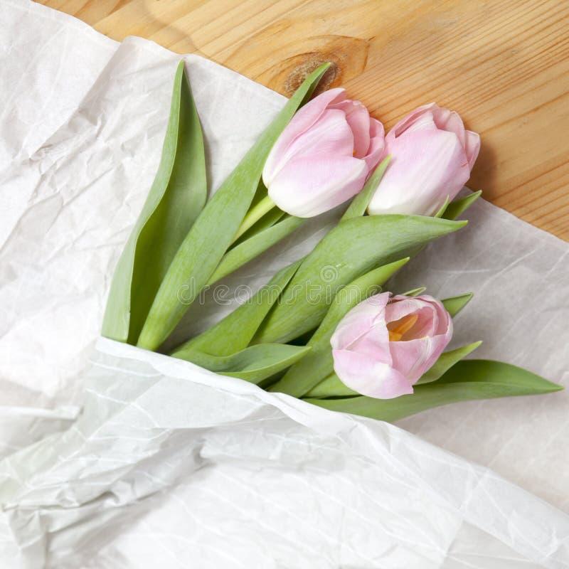 Ramalhete cor-de-rosa da tulipa do aniversário envolvido no Livro Branco Vista superior no grupo de tulipas frescas, conceito da  imagem de stock royalty free