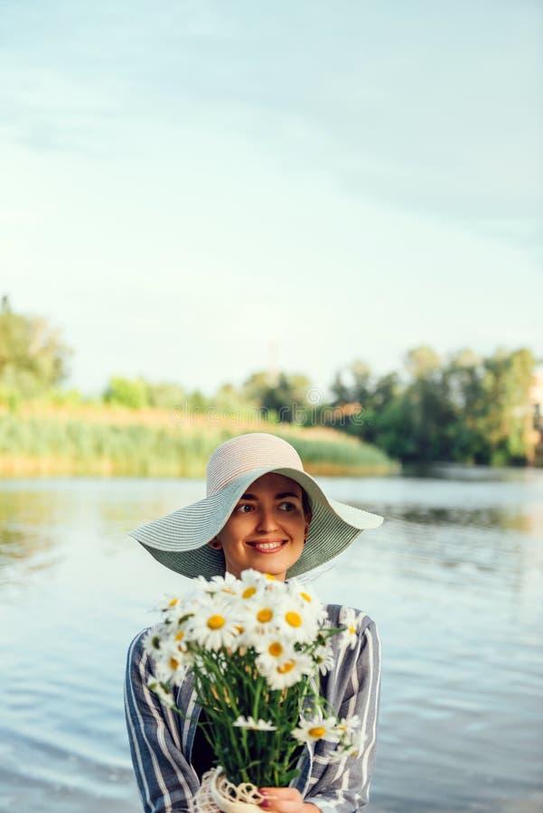 Ramalhete da camomila nas mãos da menina no fundo do rio Conceito feliz do florista Ch? de acalma??o imagem de stock royalty free