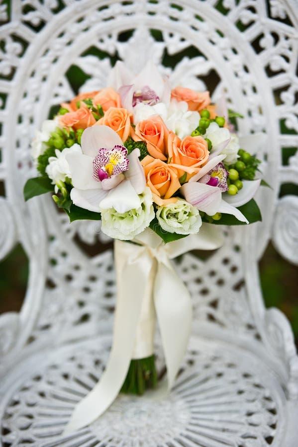 Ramalhete Da Flor Do Casamento Em Uma Cadeira De Jardim Branca Imagem de Stock Royalty Free