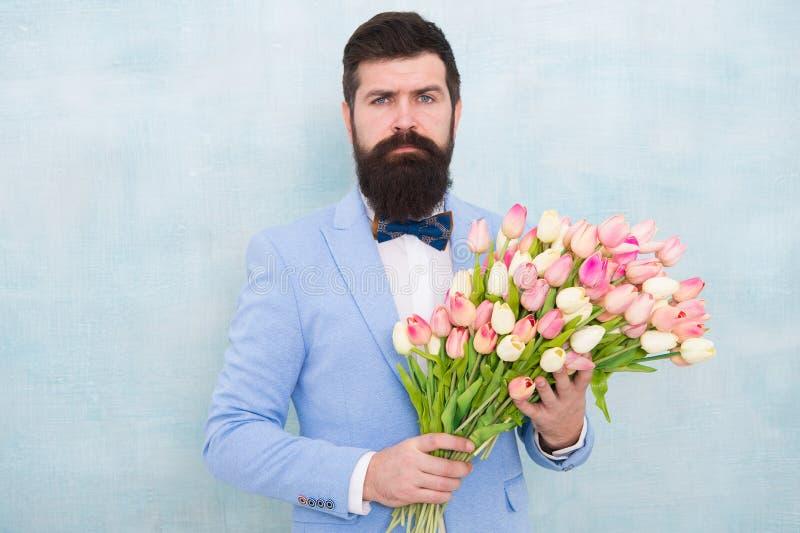 Ramalhete da mola 8 de mar?o ame a data com flores Feliz aniversario homem farpado no la?o com flores da tulipa womens imagem de stock