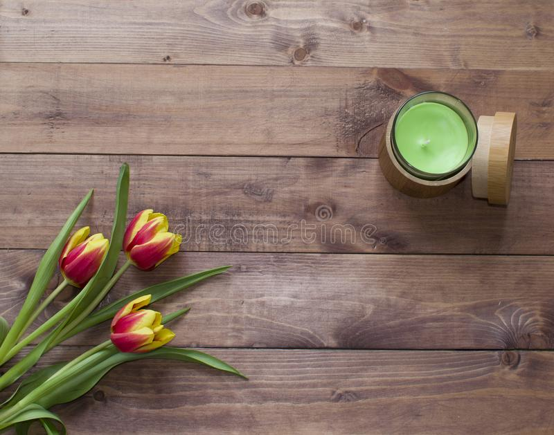 Ramalhete da P?scoa da mola de Flatlay de flores da tulipa com caixa e vela de madeira no fundo de madeira Vista com espa?o da c? imagens de stock royalty free
