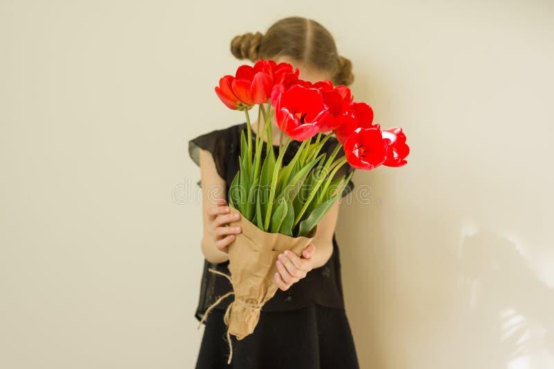 Ramalhete da terra arrendada da menina da criança de flores vermelhas das tulipas Presente, surpresa, feriado da família da mola fotos de stock