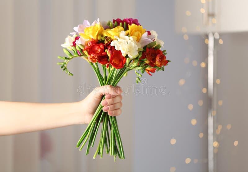 Ramalhete da terra arrendada da mulher de flores bonitas da frésia da mola imagens de stock