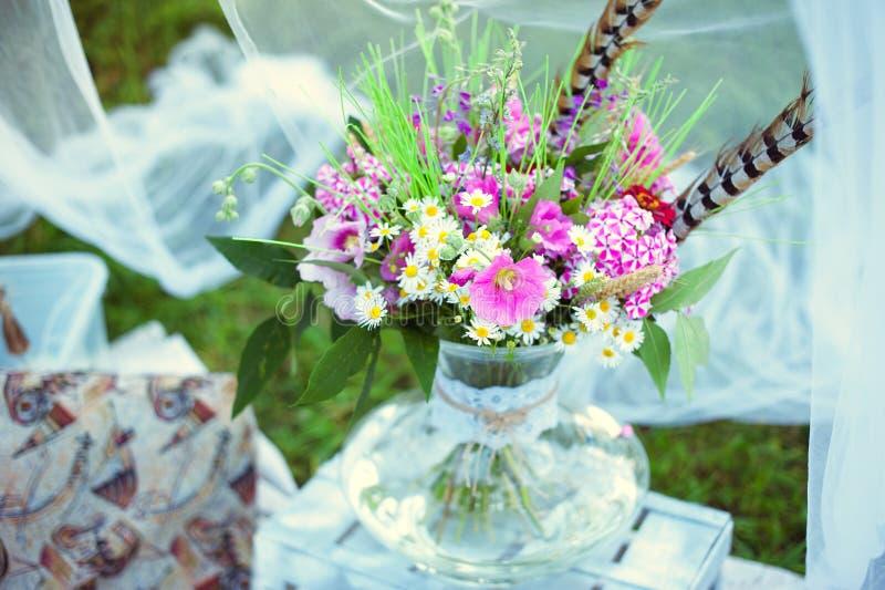 Ramalhete das flores ao estilo do boho em um vaso de vidro na natureza fotografia de stock