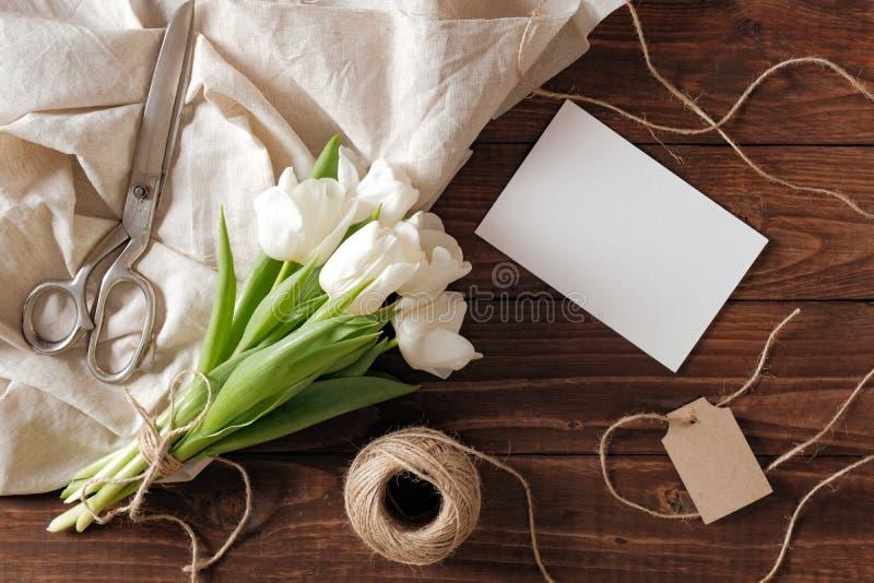 Ramalhete das flores brancas da tulipa, cartão de papel vazio da mola, tesouras, guita na mesa de madeira rústica Composição do d imagens de stock royalty free