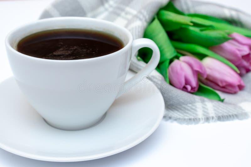Ramalhete das flores da mola, tulipas cor-de-rosa no fundo quadriculado com uma xícara de café - cartão da manta do feriado para  fotografia de stock royalty free