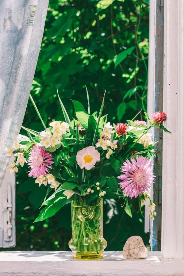 Ramalhete das flores do trevo, das centáureas e do jasmim em um vaso de vidro e de uma pedra dada forma coração na soleira de uma fotos de stock