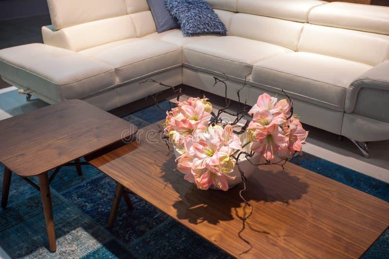 Ramalhete das flores no vaso na tabela de madeira perto do sofá de couro branco imagens de stock royalty free
