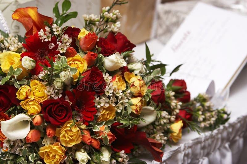 Ramalhete das noivas com um livro de convidado no fundo fotografia de stock royalty free