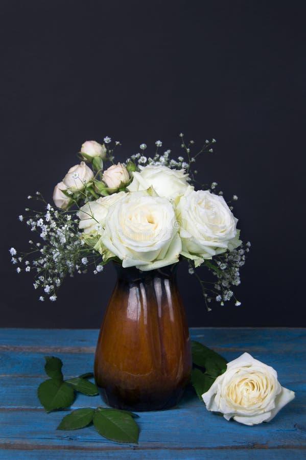 Ramalhete das rosas brancas e do gypsophila em um vaso no backgrou escuro fotografia de stock royalty free
