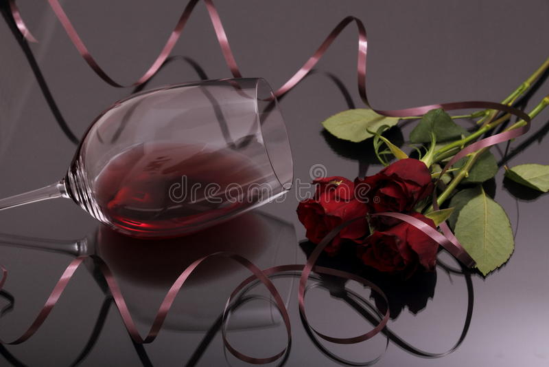 Ramalhete das rosas e do vinho tinto de vidro no preto fotografia de stock royalty free