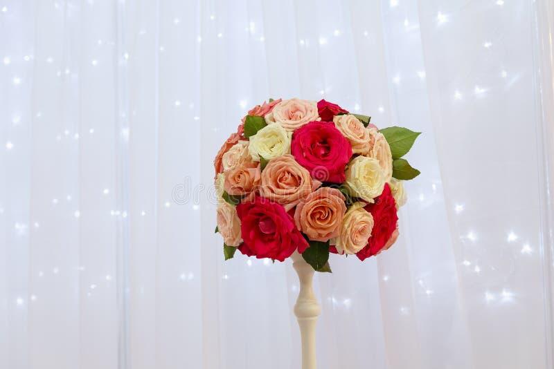 Ramalhete das rosas em um vaso no fundo de uma cortina de seda fotos de stock