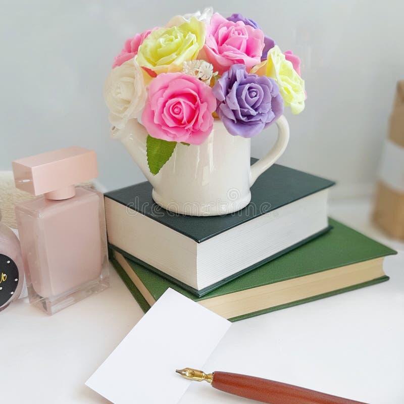 Ramalhete das rosas em um vaso, pilha de livros, cartão com a pena da montanha na tabela na frente do fundo branco fotos de stock