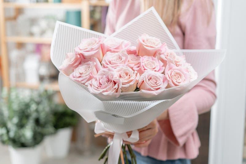Ramalhete das rosas nas mãos das mulheres Grupo pálido - rosa o conceito de um florista em um florista wallpaper foto de stock