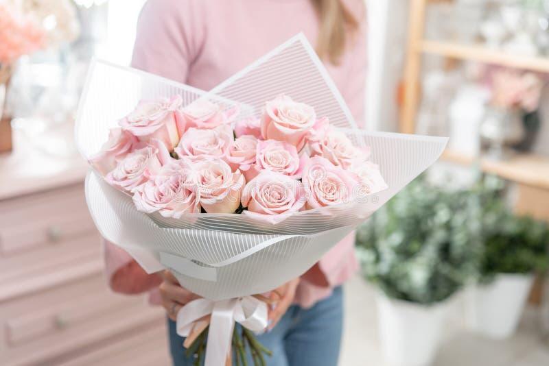 Ramalhete das rosas nas mãos das mulheres Grupo pálido - rosa o conceito de um florista em um florista wallpaper imagem de stock