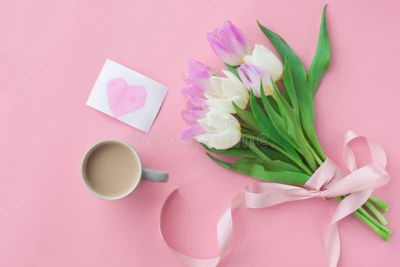 Ramalhete das tulipas e de um copo de café em um fundo pastel cor-de-rosa Café da manhã maravilhoso da mola no dia ou nas mulhere imagem de stock royalty free