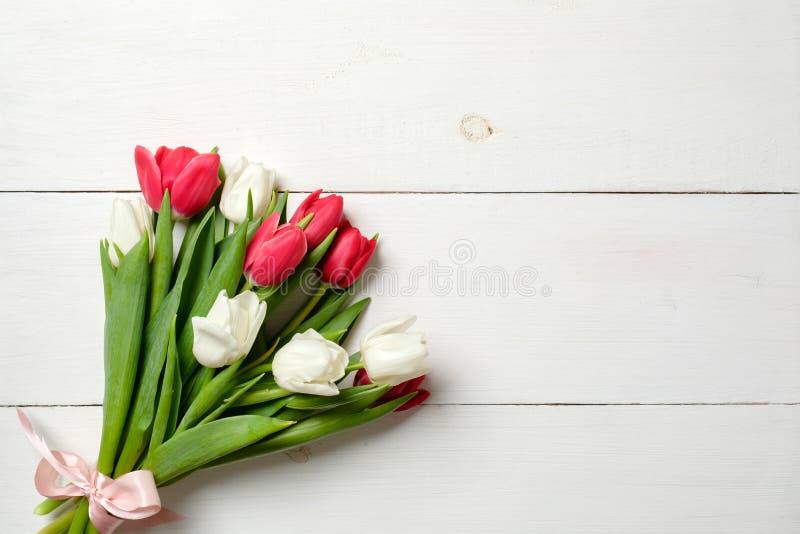 Ramalhete das tulipas na tabela de madeira branca, espaço da cópia para o texto Modelo por feriados da mola, Inte da bandeira do  imagem de stock royalty free