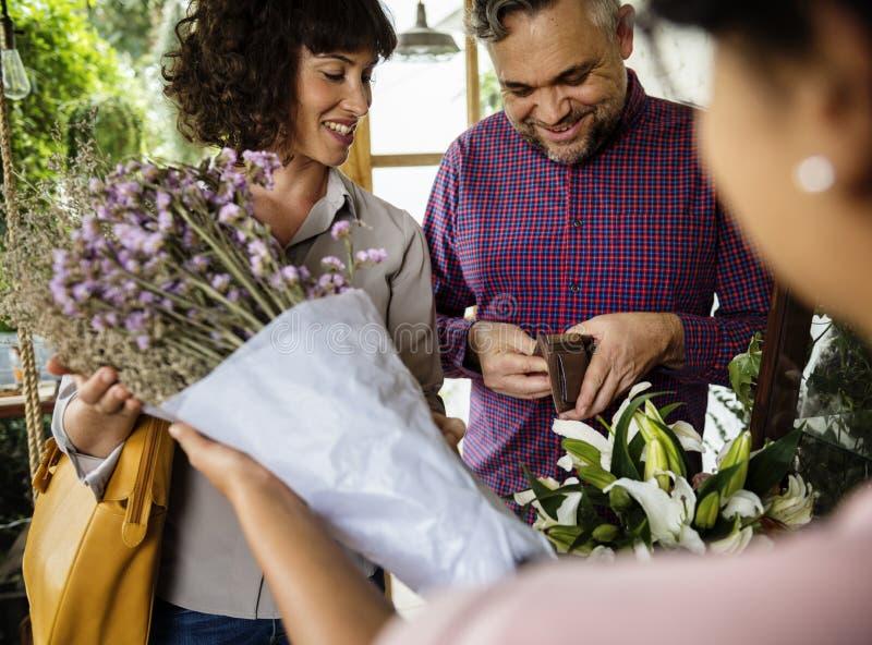 Ramalhete de compra dos povos da flor em Flora Shop foto de stock
