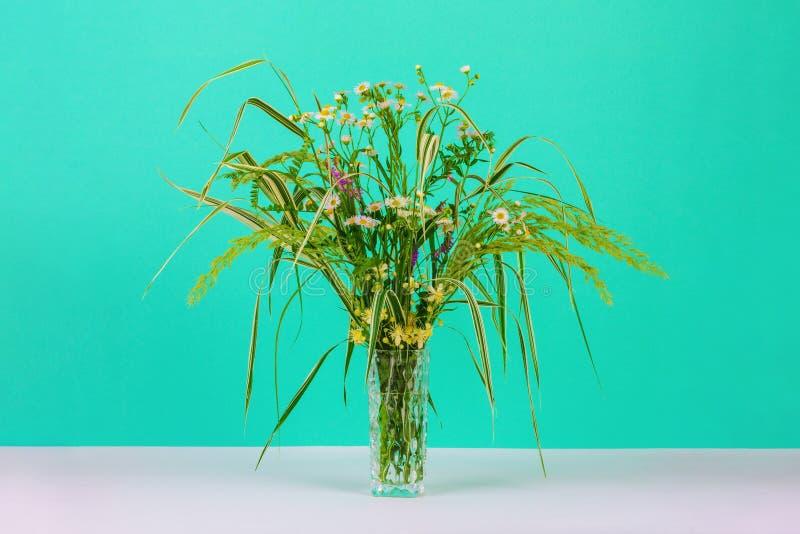 Ramalhete de ervas do verão, de margaridas e de flores da clematite em um vaso de vidro em um fundo da cor da hortelã imagem de stock royalty free