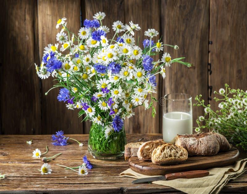 Ramalhete de flores do campo, de vidro do leite e do pão macio imagens de stock royalty free