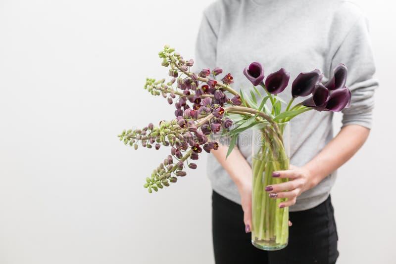 Ramalhete de flores e do Calla violeta-marrons bonitos do Fritillaria Flores da mola na mão da mulher o trabalho do florista imagem de stock