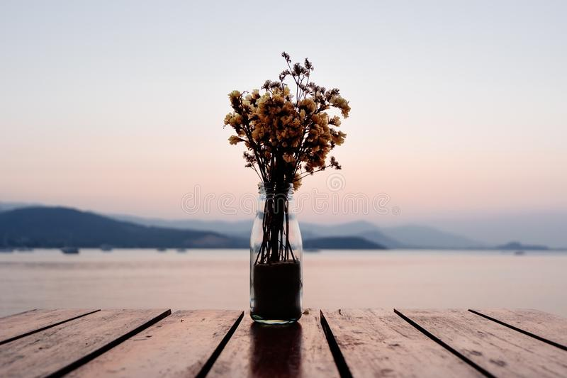 Ramalhete de flores secadas no frasco de vidro com as flores secadas na madeira imagem de stock royalty free