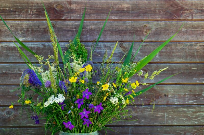 Ramalhete de flores selvagens em um fundo de madeira da parede Placas velhas, campo do russo imagens de stock royalty free