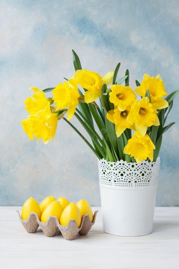 Ramalhete de narcisos amarelos amarelos frescos no vaso e em ovos decorativos no fundo dos azul-céu foto de stock royalty free