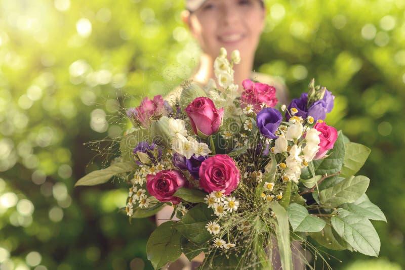Ramalhete de oferecimento da mulher de flores frescas na câmera imagem de stock