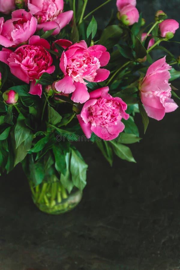 ramalhete de peônias cor-de-rosa-roxas em um vaso em um fundo escuro foto de stock