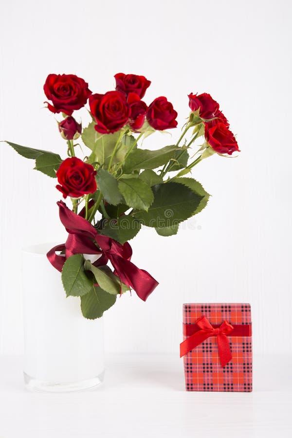 Ramalhete de rosas vermelhas com a caixa de presente vermelha no fundo branco imagens de stock