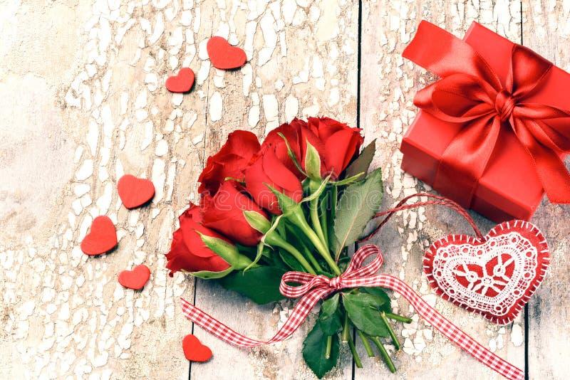 Ramalhete de rosas vermelhas com coração e presente decorativos St Valen imagens de stock