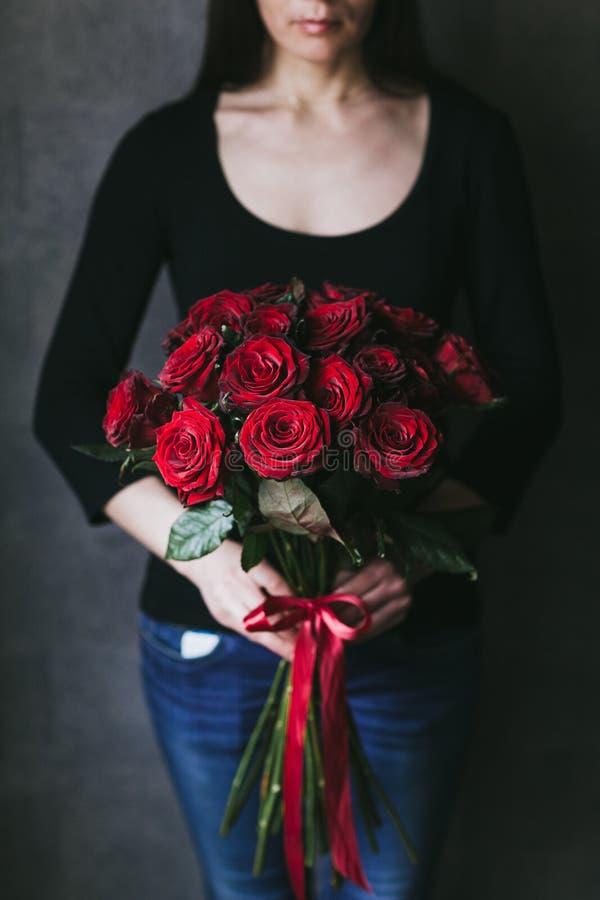 Ramalhete de rosas vermelhas nas m?os de uma mulher fotografia de stock royalty free
