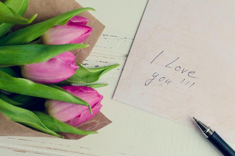Ramalhete de tulipas cor-de-rosa com notas EU TE AMO imagens de stock