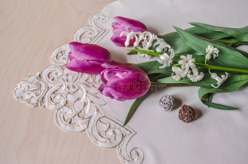 Ramalhete de tulipas roxas e do jacinto branco com chocolates fotos de stock