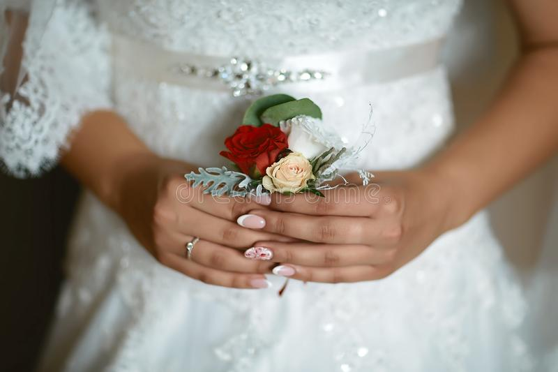 Ramalhete delicado bonito do casamento da flor e com as flores brancas e vermelhas nas mãos do ` s da noiva em um vestido do laço fotos de stock