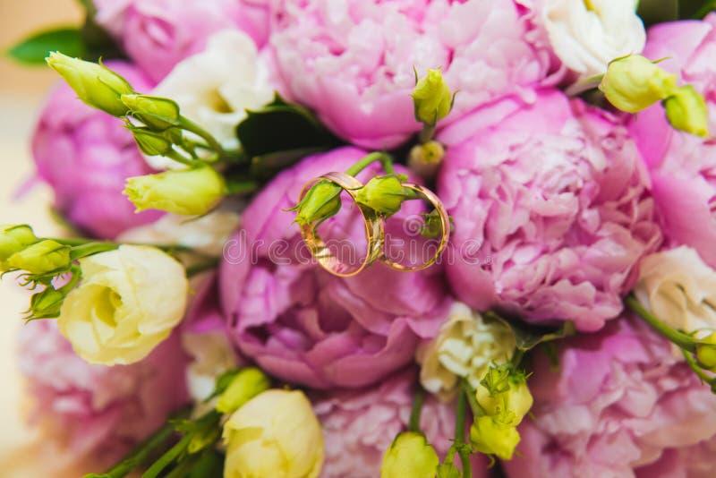 Ramalhete delicado bonito do casamento de peônias e das alianças de casamento cor-de-rosa dos noivos imagens de stock