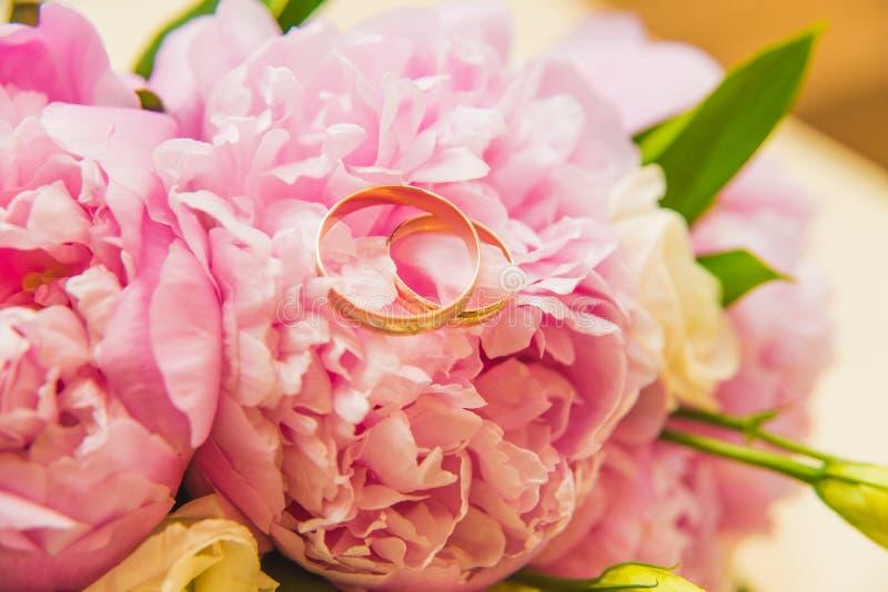 Ramalhete delicado bonito do casamento de peônias e das alianças de casamento cor-de-rosa dos noivos imagem de stock royalty free