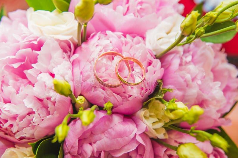 Ramalhete delicado bonito do casamento de peônias e das alianças de casamento cor-de-rosa dos noivos foto de stock