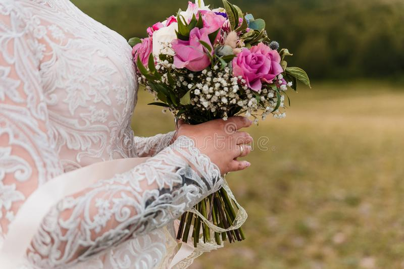 Ramalhete delicado das rosas nas mãos da noiva em um fundo borrado fotografia de stock