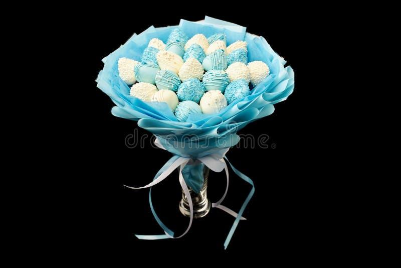 Ramalhete delicioso das morangos cobertas com o chocolate branco e azul em um fundo preto fotos de stock