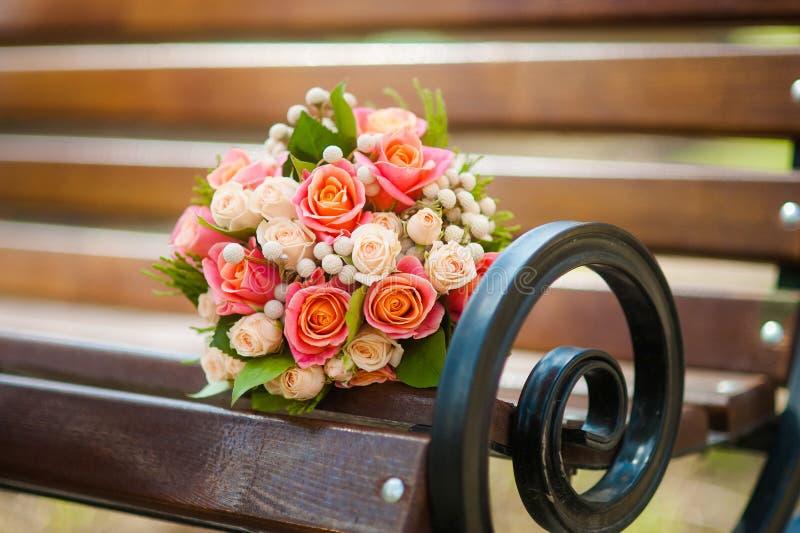 Ramalhete do casamento com rosas em um banco de madeira foto de stock