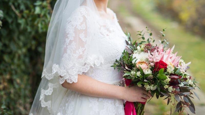 Ramalhete do casamento da beleza no bride& x27; mãos de s imagem de stock