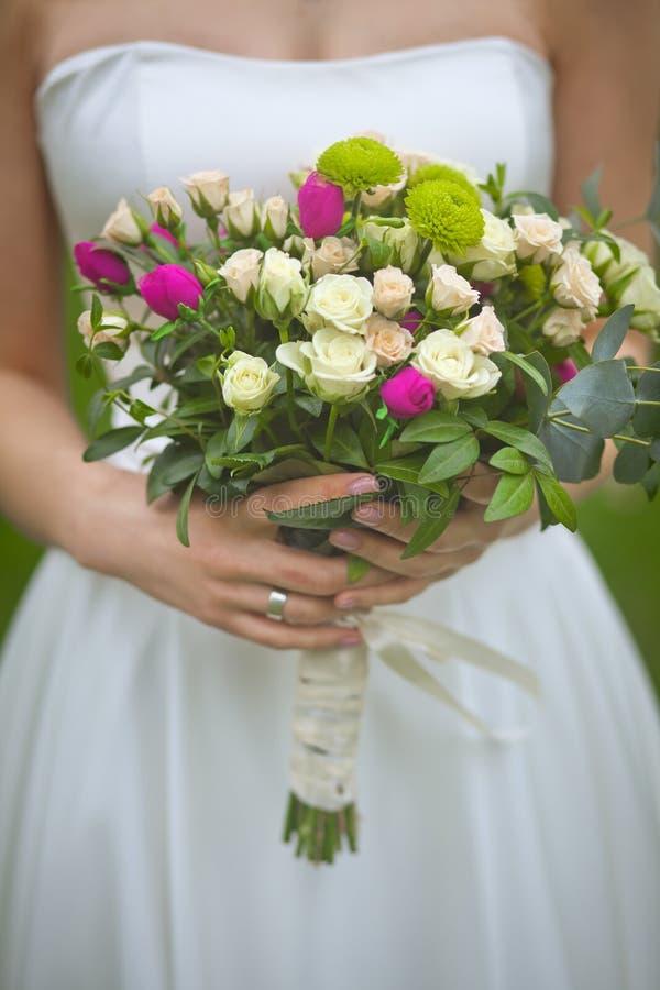 Ramalhete do casamento da mola nas mãos da noiva imagens de stock royalty free